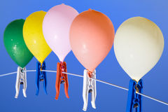 Up. Group of colored water filled balloons with waterdrops hanging on a clothesline with a blue sky as background, from below Royalty Free Stock Image