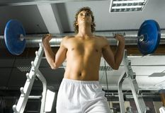 And up!. Young weightlifter with naked chest picking up heavy bar-bell. Low angle view Royalty Free Stock Photos