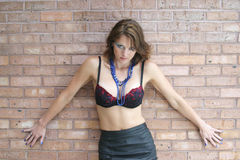 Up against a wall. Woman in bra against a brick wall Royalty Free Stock Photography