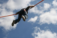 Up in the air. Boy in the air after bungee jumping on a trampoline Royalty Free Stock Photos