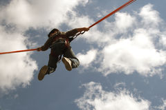 Up in the air. Young boy jumps with bungee on a trampoline Stock Image