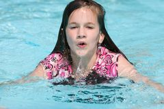 Up For Air. Swimming preteen girl, coming out of the pool water for air royalty free stock photography