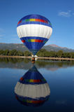 Up and away, No down and wet. Hot air balloon taking on water, too heavy now, with water in basket stock image