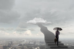 Up the career ladder. Businessman holding umbrella and waking on career ladder Stock Images