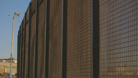 Up Close Border Fence by Highway. Tight shot of the United States and Mexico border fence with traffic passing in the background stock video footage