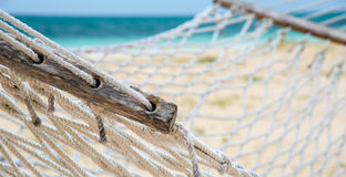 Up close hammock on a tropical beach. Intricate details of an empty hammock on a tropical beach with the Caribbean ocean in the background Royalty Free Stock Image