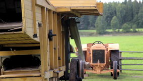 Up close image of the working old antique straw hammer mill tractor. A very up close image of the straw hammer mill working and processing the products making stock video footage