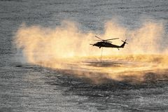 Helicopter descending onto water royalty free stock image