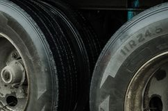 Up close to the tires of a cargo truck, black tires with dirt caused by rain in a city stock image