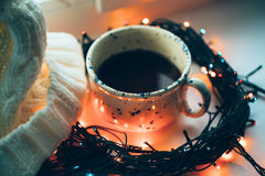 Сup of coffee and Christmas lamp garland Royalty Free Stock Photo