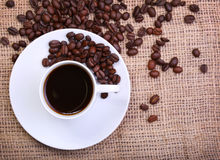 Сup of coffee over burlap background. Top of view Stock Images