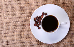 Сup of coffee over burlap background. Top of view Royalty Free Stock Photography