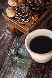 Сup of coffee, pine cones in basket, walnuts and cinnamon sticks Stock Photos