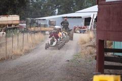 Up det bärande folket för traktor i bilar för koleksakdrev grusvägen royaltyfri bild