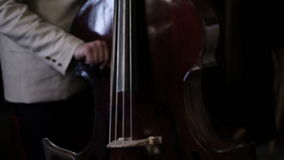Up and down close pan shot of a bass player stock footage