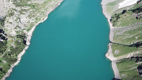 Up and down drone aerial view of the Lake Barbellino an alpine artificial lake. Italian Alps. Italy. Summer time stock footage