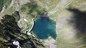 Up and down drone aerial view of the small and lower Lake Barbellino an alpine artificial lake. Italian Alps. Italy. Summer time stock footage