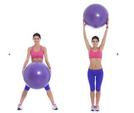 Up and down. Fit woman doing exercise with a swiss ball in standing position and holds down the ball. (A) Lift up the ball in standing position. (B stock photo