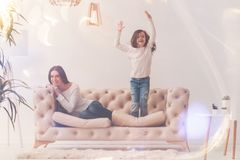 Energetic goofy kid jumping up on sofa royalty free stock photo