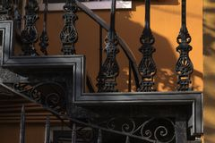 The up and down stairs. Iron stairs with design a background of orange.  Shot in New Orleans Royalty Free Stock Images