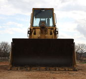 Up front bull dozer. The front of a yellowish gold bull dozer with a cloudy sky background royalty free stock images
