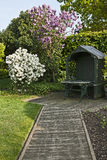 Up the Garden Path. View of a decked path and seat with shrubs in full bloom Royalty Free Stock Photo