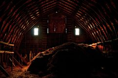 Up in the Hayloft. A haystack remains in the the hayloft of an old barn with light shining through the windows and door cracks Stock Photography