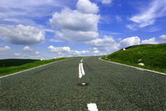 Up the Hill and Round the Bend. Mountain road from a low angle with a right hand bend in the distance, set against a blue sky with puffy white clouds. Located stock images