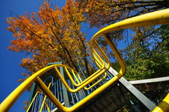 Up the ladder. A playground ladder with a tree in autumn colors and clear blue sky Royalty Free Stock Photos