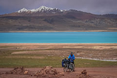 Up the mountain pass. Woman pushing her bicycle uphill on a difficult mountain road on a tibetan plateau, Tibet Royalty Free Stock Photography