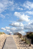 Up the path. Blue sky with clouds, dunes and a path with some people Royalty Free Stock Photos