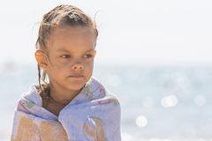 Up portrait of five year old girl wrapped in a towel on the background of the sea Stock Images