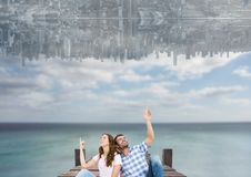 up side down city in the sky over the sea with couple sit on a dock and looking up Stock Photo