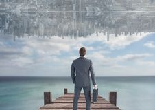 up side down city in the sky over the sea with dock. Men looking up. Stock Photos
