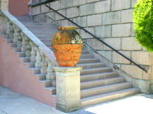 Up the stairs. Red claypot on pedestal at bottom of stairs, in garden of museum royalty free stock images