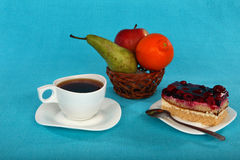 Сup of tea, cake and fruit in basket Royalty Free Stock Image