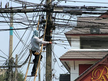 Up to code?. An electrical worker fixing a wire on a seemingly overloaded electrical pole. Taken in Chiang Mai, Thailand Royalty Free Stock Photos