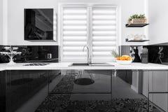 Up-to-date stylish kitchen. Up-to-date decor of stylish kitchen with shining black and white units Royalty Free Stock Photo