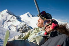 Up to the top of the mountain. A young smiling couple in front of a beautiful background winter and climb to the mountain with vaha lift Stock Images