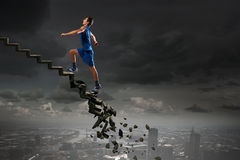 Up to top overcoming challenges. Sports active man running on stone collapsing ladder stock images