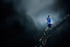 Up to top overcoming challenges. Sports active man running on stone collapsing ladder stock photo