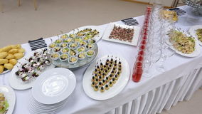 Up view of banquet table with appetizers, canapes, plates and glasses. There is tasty food served such as patty baked, lots of white clean plates and number of stock video footage