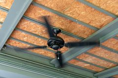 Up view Black Ceiling Fan running in home stock photos