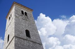 Old stone bell tower, a view from below, with a background of blue sky and snowy white clouds royalty free stock photo