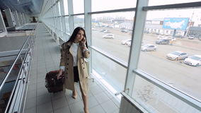 Up view of young female going down airport hall. Fashionable and beautiful woman is talking on cell phone walking down corridor with big portrait windows. She stock video