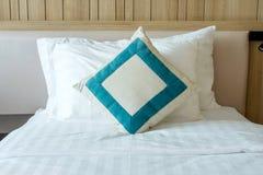 Upaćkany biały łóżkowy comforter z dekoracyjnymi poduszkami w sypialni zdjęcie royalty free