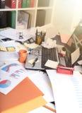 Upaćkany i cluttered biurko, lekki skutek fotografia stock