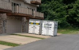 UPack moving containers on drive of townhouse Royalty Free Stock Photos