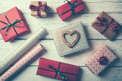 upakowani prezenty i opakunkowy papier na białym drewno stole zdjęcia royalty free