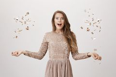 Upbeat attractive female model tossing golden confetti with spreaded hands, standing amazed or surprised in trendy. Evening dress over gray background. Girl was Stock Photography